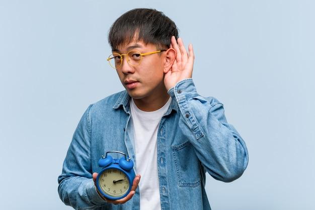 Молодой китайский человек, держащий будильник, пытается слушать сплетни