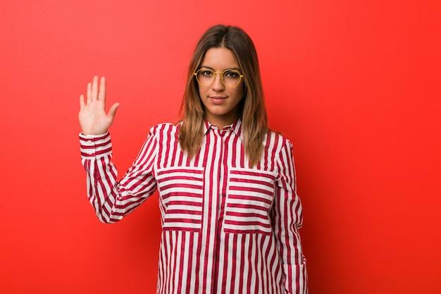 Молодая харизматичная девушка улыбается веселый показ номер пять с пальцами