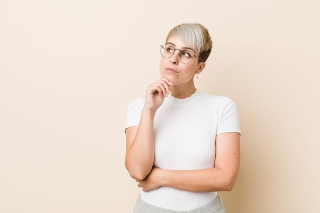 疑わしいと懐疑的な表情で横に見て白いシャツを着ている若い本物の自然な女性