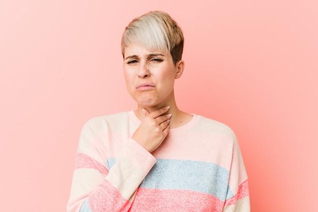 自然な曲線美の若い女性は、ウイルスや感染症により喉の痛みに苦しんでいます。