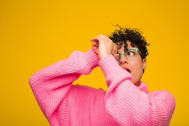 Молодая афро-американская женщина нося розовый свитер смотря далеко держать руку на лбу