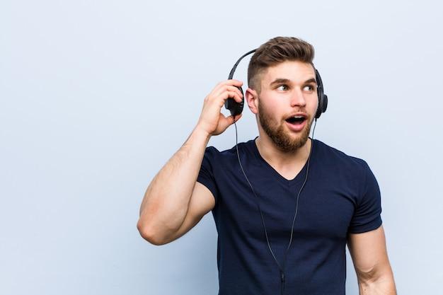 Молодой кавказский человек слушая к музыке пробуя слушать сплетню