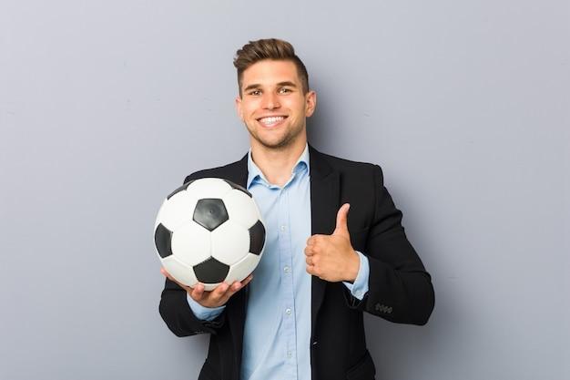 Молодой тренер по футболу улыбается и поднимает палец вверх