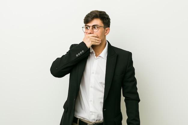 手で口を覆っているコピースペースを探している思慮深い若いビジネスヒスパニック男