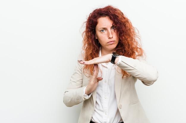 タイムアウトジェスチャーを示す若い自然な赤毛ビジネス女性