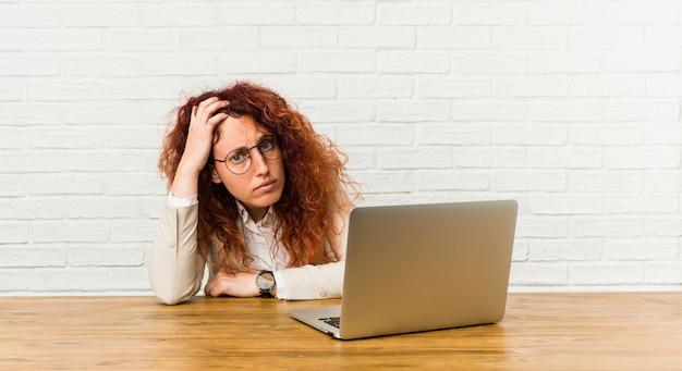 彼女のラップトップでショックを受けている若い赤毛の巻き毛の女性、彼女は重要な会議を思い出した