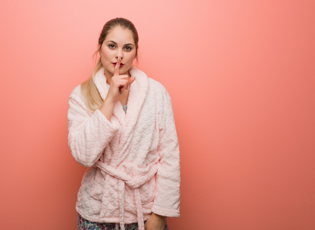 秘密を守るか沈黙を求めるパジャマを身に着けている若いロシア人女性