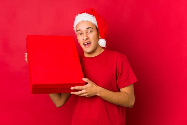 Молодой человек держит подарок на рождество