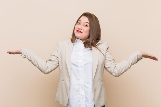 若いビジネス女性を疑い、質問ジェスチャーで肩をすくめ。