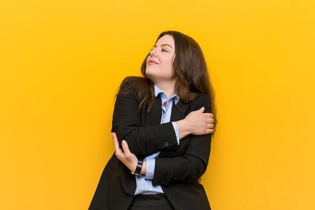 Молодой плюс размер кавказской деловой женщины обнимает себя, улыбается беззаботной и счастливой.