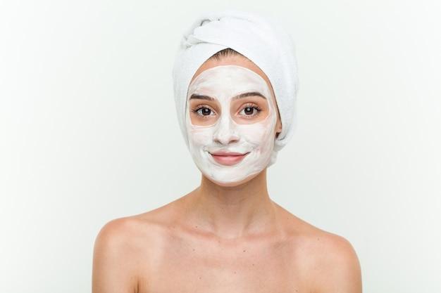 顔のマスク治療を楽しんでいる若い白人女性
