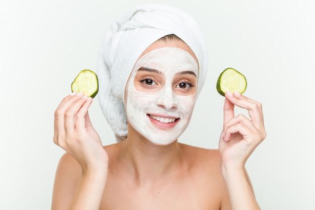 キュウリと顔のマスク治療を楽しんでいる若い白人女性