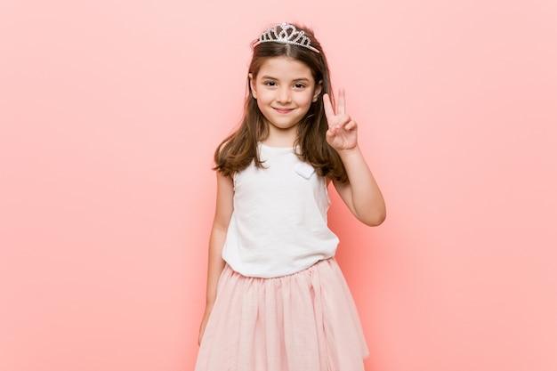 勝利のサインを示し、広く笑顔のプリンセスルックを着ている少女。