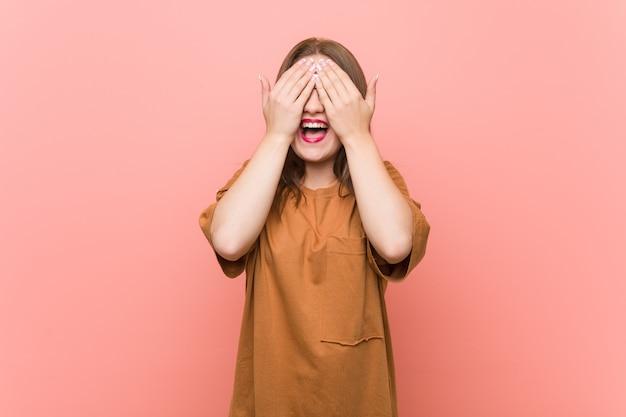 眼鏡をかけている若い学生女性が手で目を覆って、驚きを広く待っている笑顔。