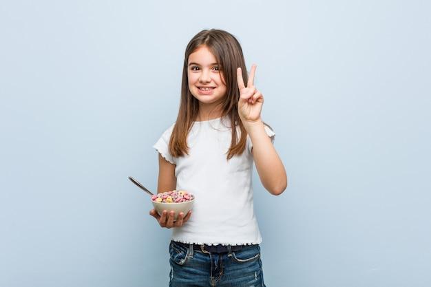 Маленькая кавказская девушка держа шар хлопьев показывая номер два с пальцами.