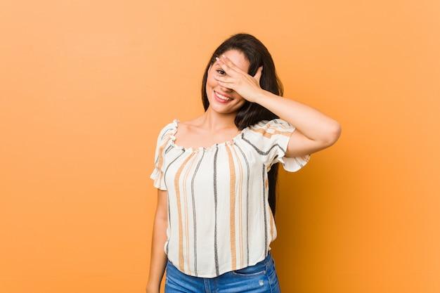 曲線の若い女性は、顔を覆う恥ずかしい指を通してカメラで点滅します。