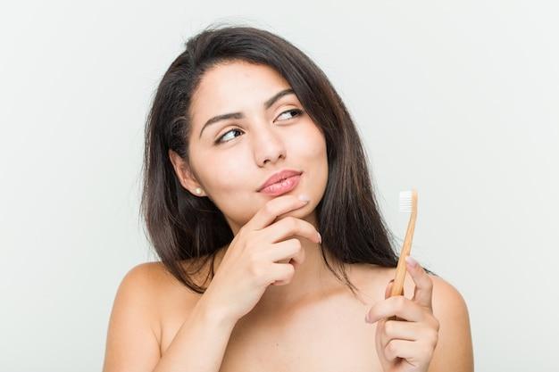 Молодая испанская женщина, держащая зубную щетку, глядя в сторону с сомнительным и скептическим выражением.