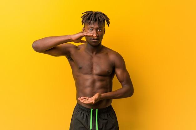 製品プレゼンテーション、両手で何かを保持している上半身裸の水着を着ている若い黒人男性。