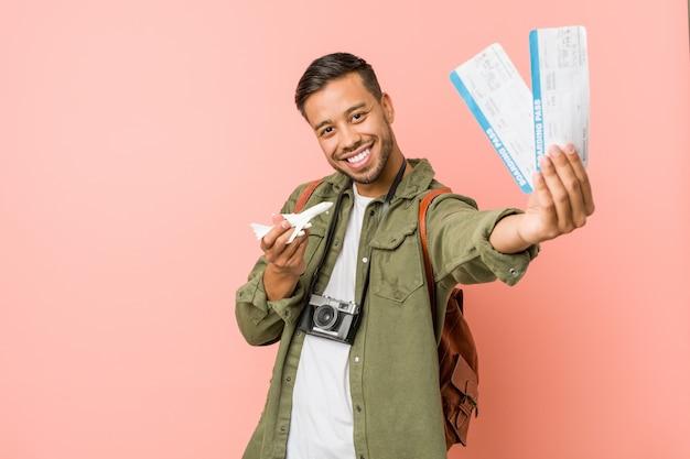 航空券を持っている若い南アジアの旅行者。