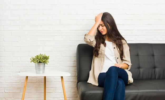 Молодая арабская женщина сидит на диване, забывая что-то, хлопая по лбу ладонью и закрывая глаза.