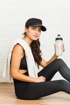 座っている若いアラブスポーティな女性と水を飲む