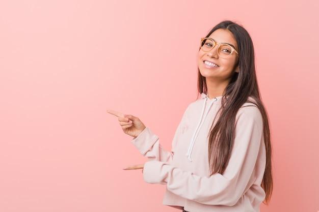 カジュアルなスポーツの外観を身に着けている若いかなりアラブの女性は、人差し指で指さし興奮しています。