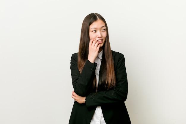 Молодая милая китайская бизнес-леди ослабила думать о что-то смотря космос экземпляра.