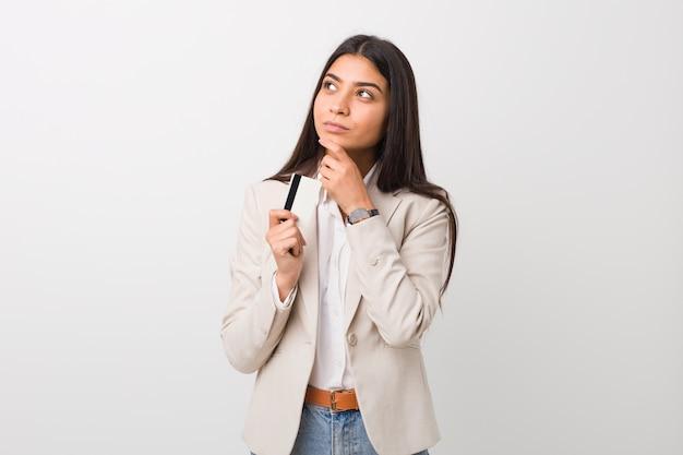 Молодая арабская женщина держа кредитную карточку смотря косой с сомнительным и скептическим выражением.