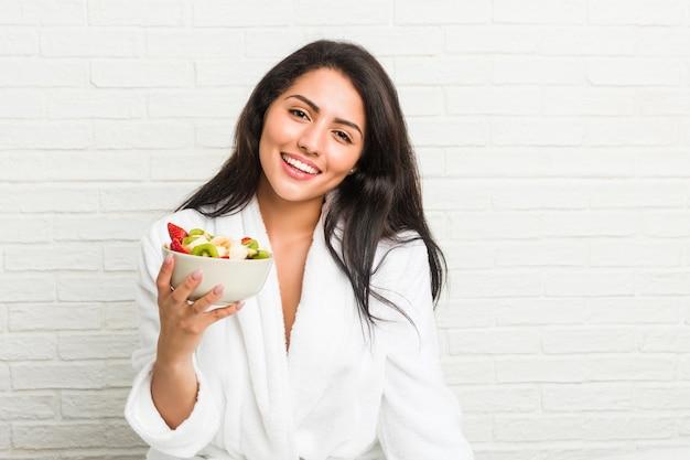 ベッドの上のフルーツボウルを食べる若いヒスパニック系女性