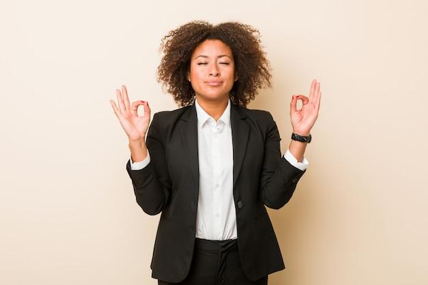 Молодой бизнес афро-американских женщина расслабляется после тяжелого рабочего дня, она выполняет йоги.