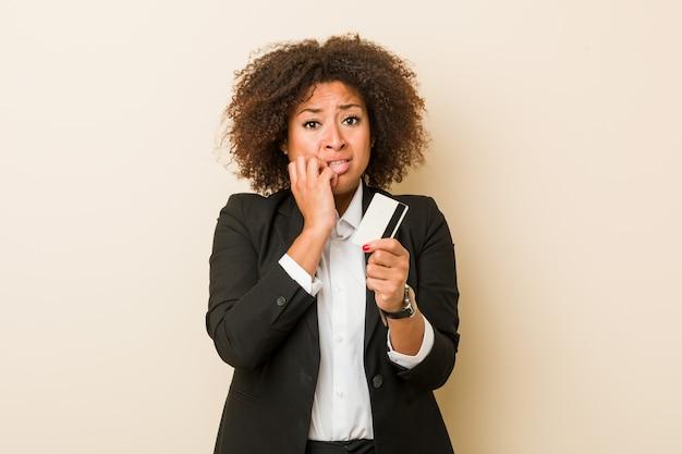 爪をかむ神経質で非常に不安なクレジットカードを保持している若いアフリカ系アメリカ人女性。