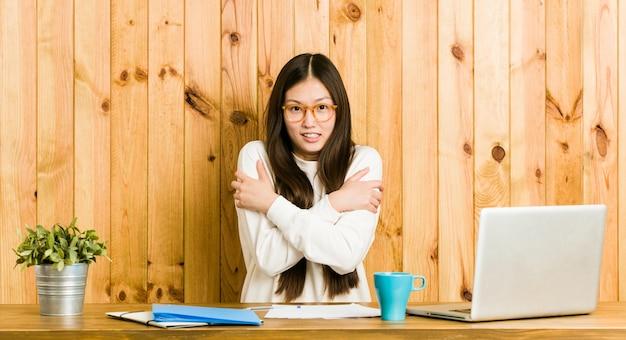 低温や病気のために机の上で勉強している若い中国人女性。