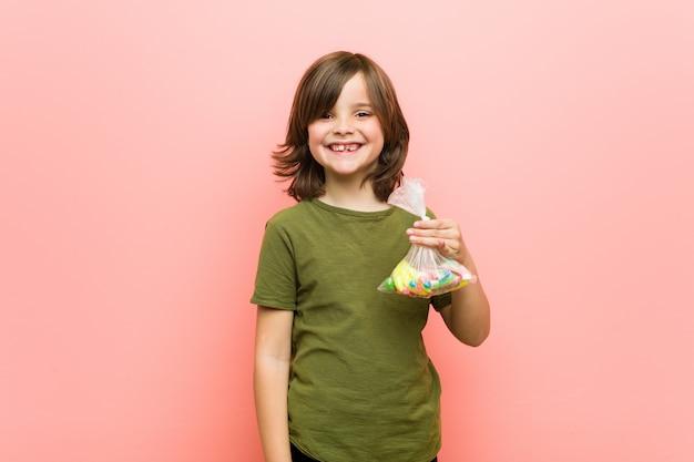 Конфеты мальчика кавказские держа счастливые, усмехающся и жизнерадостные.
