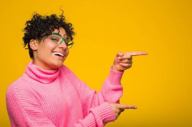 Молодая афро-американская женщина нося розовый свитер возбудила указывать с указательными пальцами прочь.