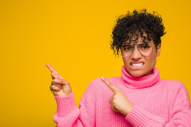 Молодая афро-американская женщина нося розовый сотрясенный свитер указывая с указательными пальцами к космосу экземпляра.