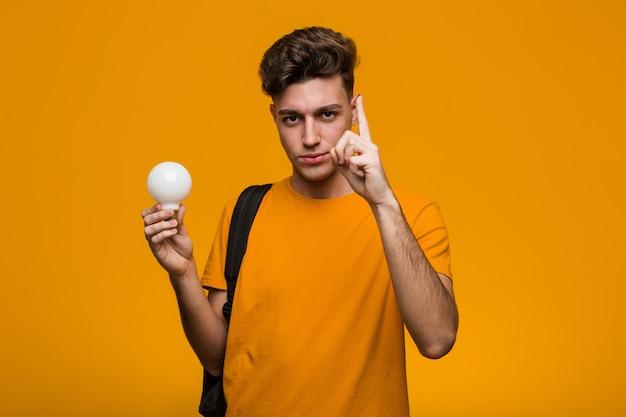 Молодой студент мужчина держит лампочку, показывая номер два с пальцами.