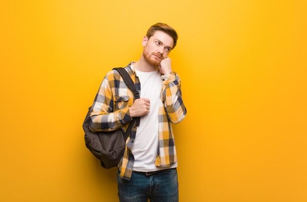 Молодой рыжий студент мужчина думает о чем-то, глядя в сторону