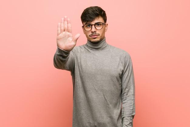 若いスマート学生男が差し出された手で一時停止の標識を表示して立っているあなたを防ぎます。