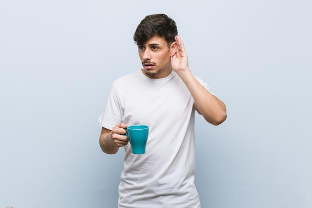 ゴシップを聴こうとしてカップを保持しているヒスパニック青年。