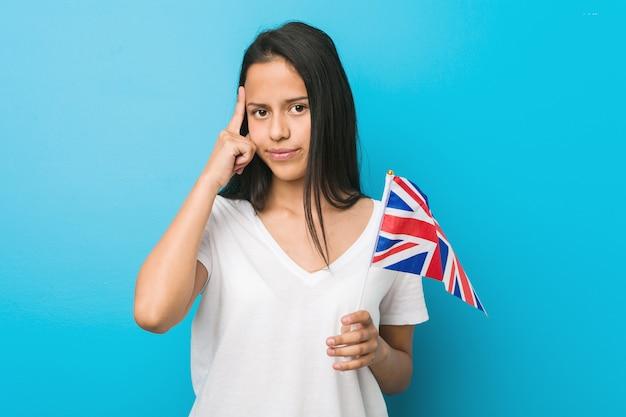 考えて、指で彼の寺院を指しているイギリス国旗を保持している若いヒスパニック系女性