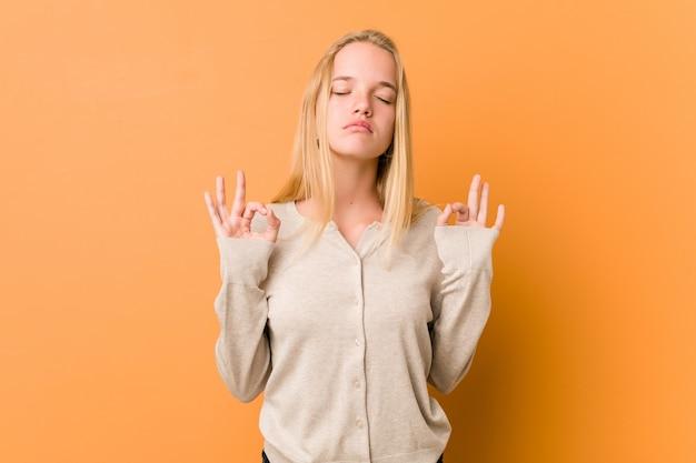 Симпатичная и естественная женщина подростка расслабляется после тяжелого рабочего дня, она выполняет йогу.