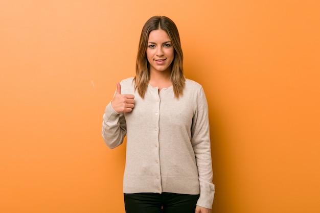 笑顔と親指を上げる壁に対して若い本物のカリスマ的な実在の女性