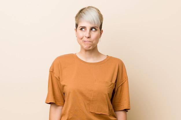 短い髪の若いプラスサイズの女性は混乱し、疑わしく不安を感じます。