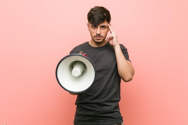 Молодой испанский человек держа мегафон указывая его висок с пальцем, думая, сфокусировал на задаче.