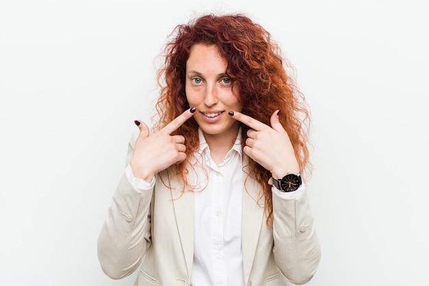 口に指を指して、白い背景笑顔に対して分離された若い自然な赤毛ビジネス女性。