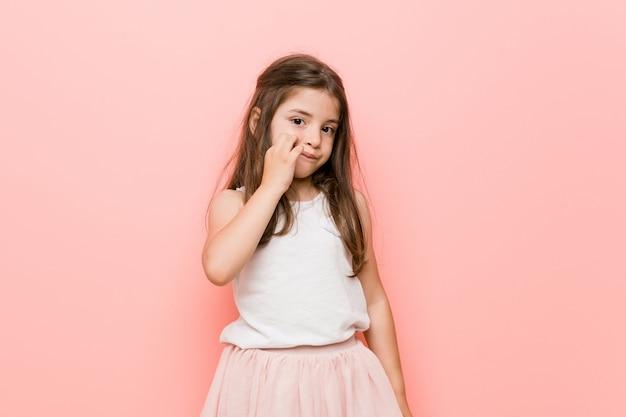 Маленькая девочка носить взгляд принцессы с пальцами на губах, сохраняя в тайне.