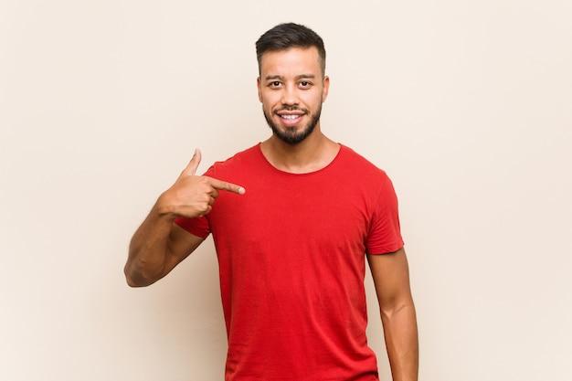 Молодой человек южно-азиатского человека, указывающий рукой на пространство копии рубашки, гордый и уверенный
