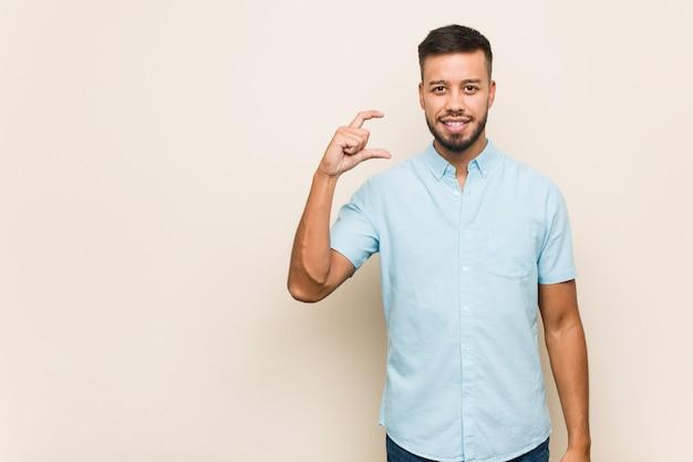 Молодой южно-азиатский мужчина держит что-то мало с указательными пальцами, улыбаясь и уверенно.