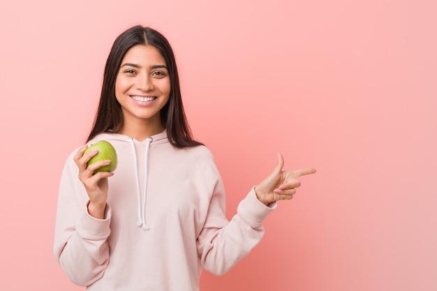 リンゴを保持している若いインド人女性