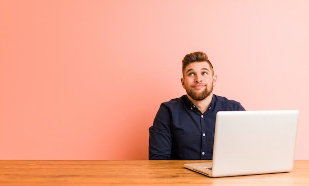 Молодой человек работает со своим ноутбуком мечтает о достижении целей и задач